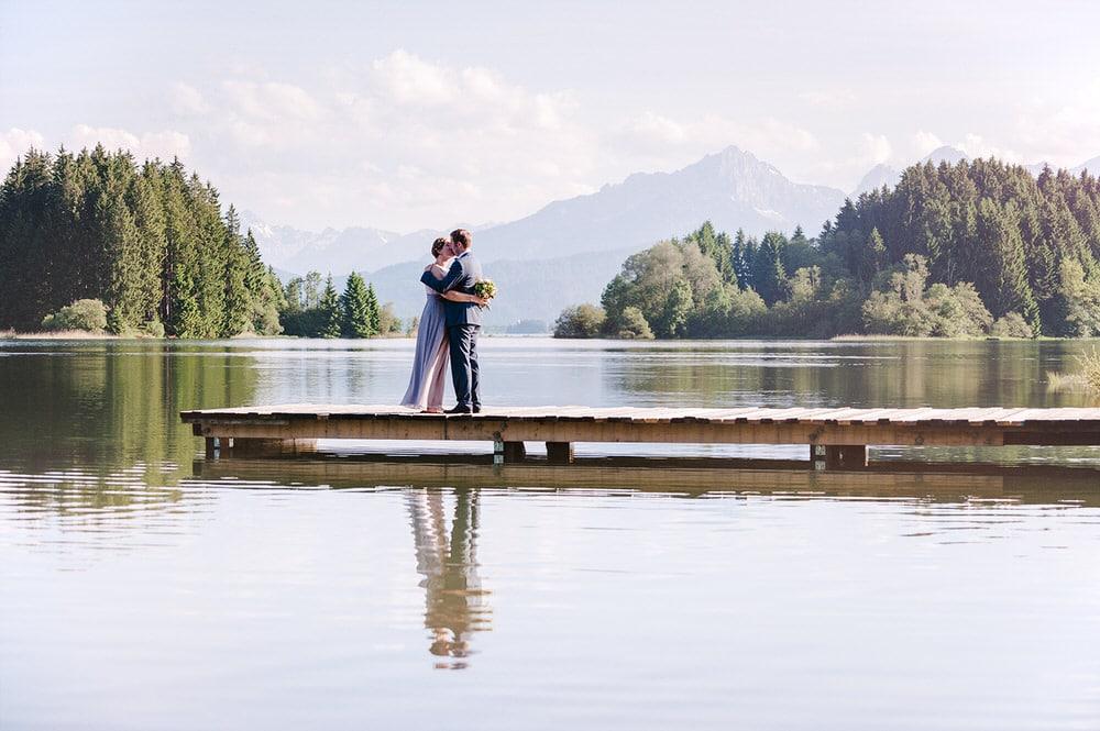 Hochzeitsfotograf Osnabrück Münster Bielefeld Moritz Fähse |Fotoshooting am See mit Brautpaar auf einem Steg vor den Alpen