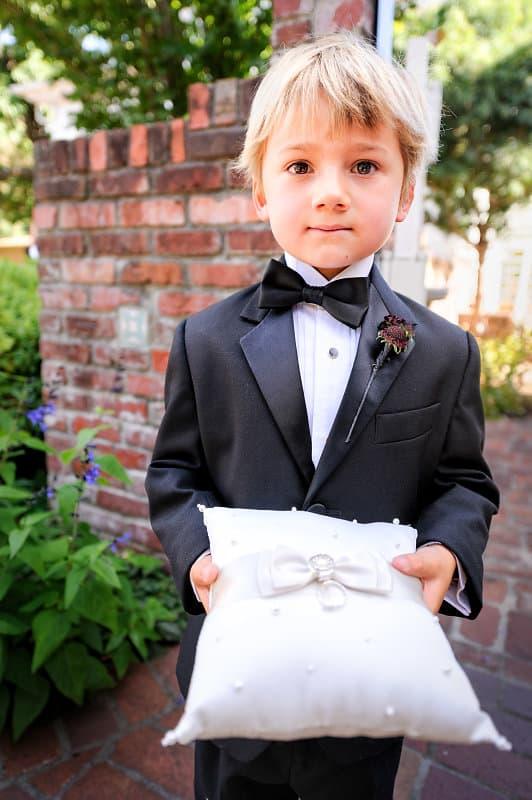 Kleiner Junge trägt das Ringkissen bei der Trauung von Lauren & Mark in Kalifornien